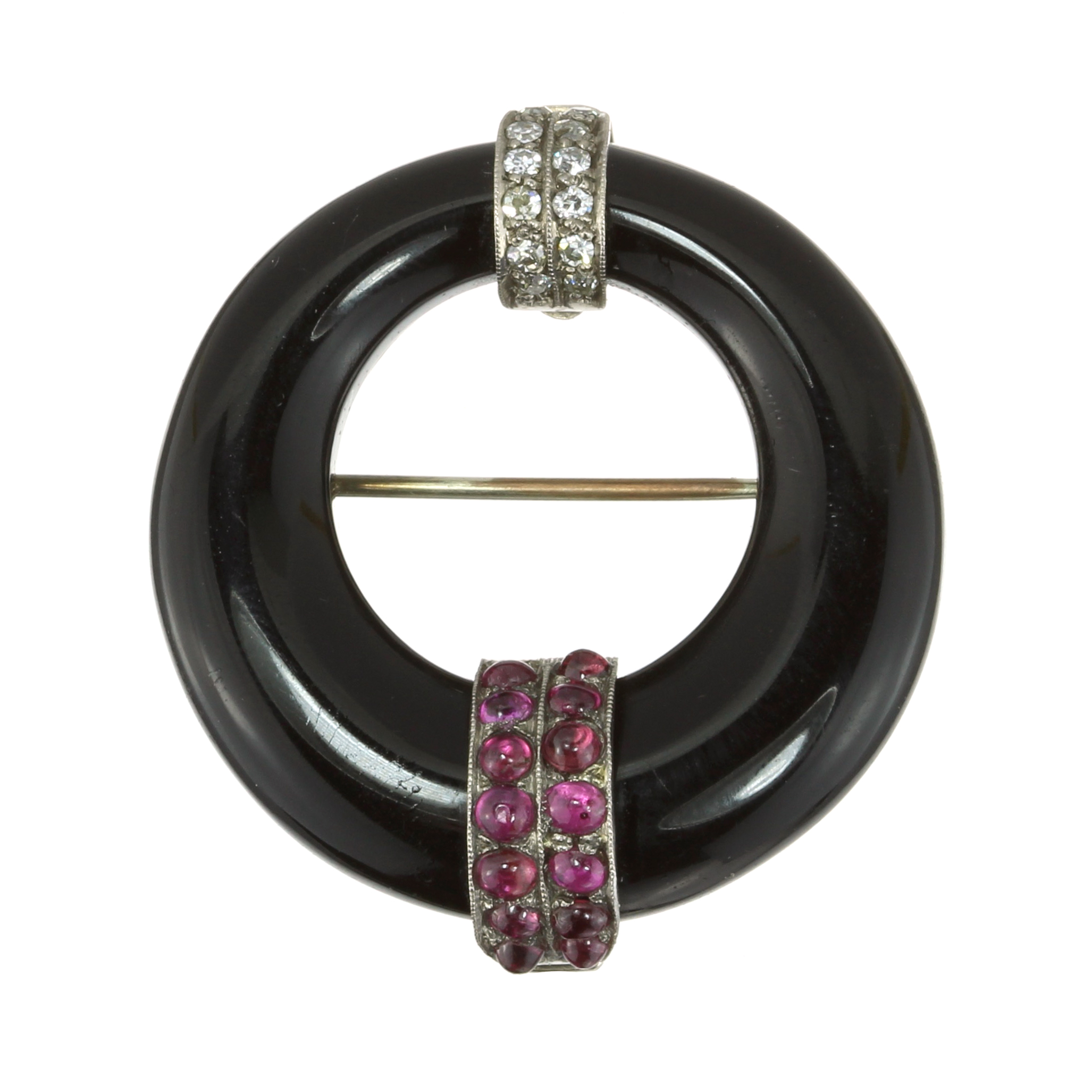 AN ANTIQUE ART DECO ONYX, RUBY AND DIAMOND BROOCH in 18ct white gold designed as a graduated black