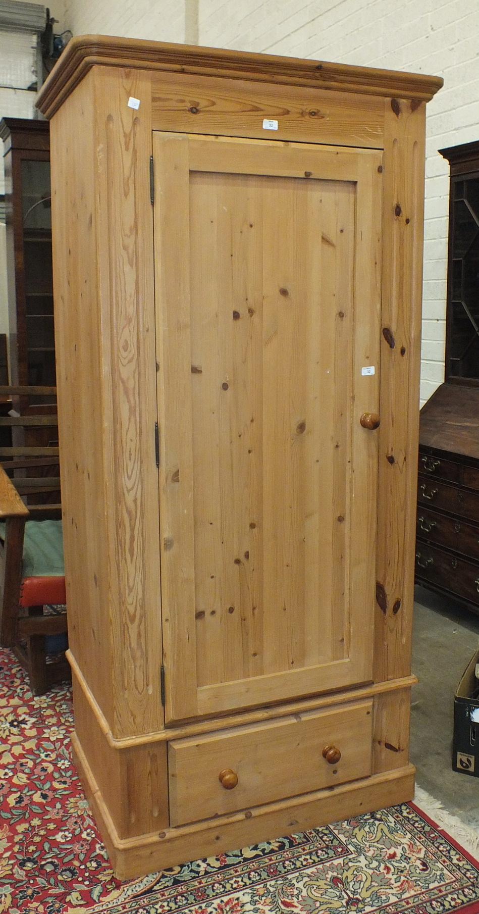Lot 32 - A modern pine single-door wardrobe on drawer base, 95cm wide.