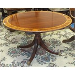 A reproduction mahogany circular dining table with inlaid and cross-banded decoration, on single