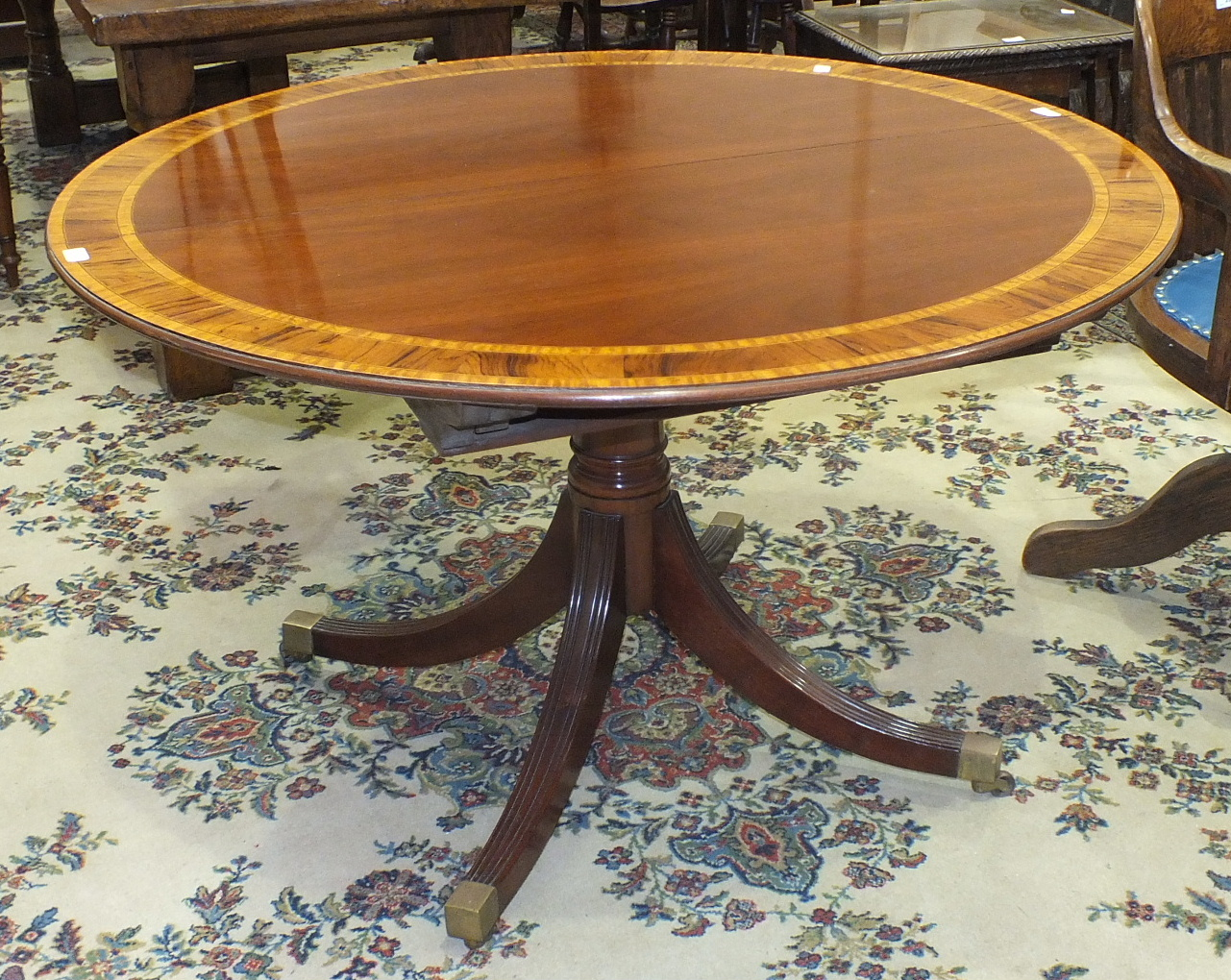 Lot 4 - A reproduction mahogany circular dining table with inlaid and cross-banded decoration, on single