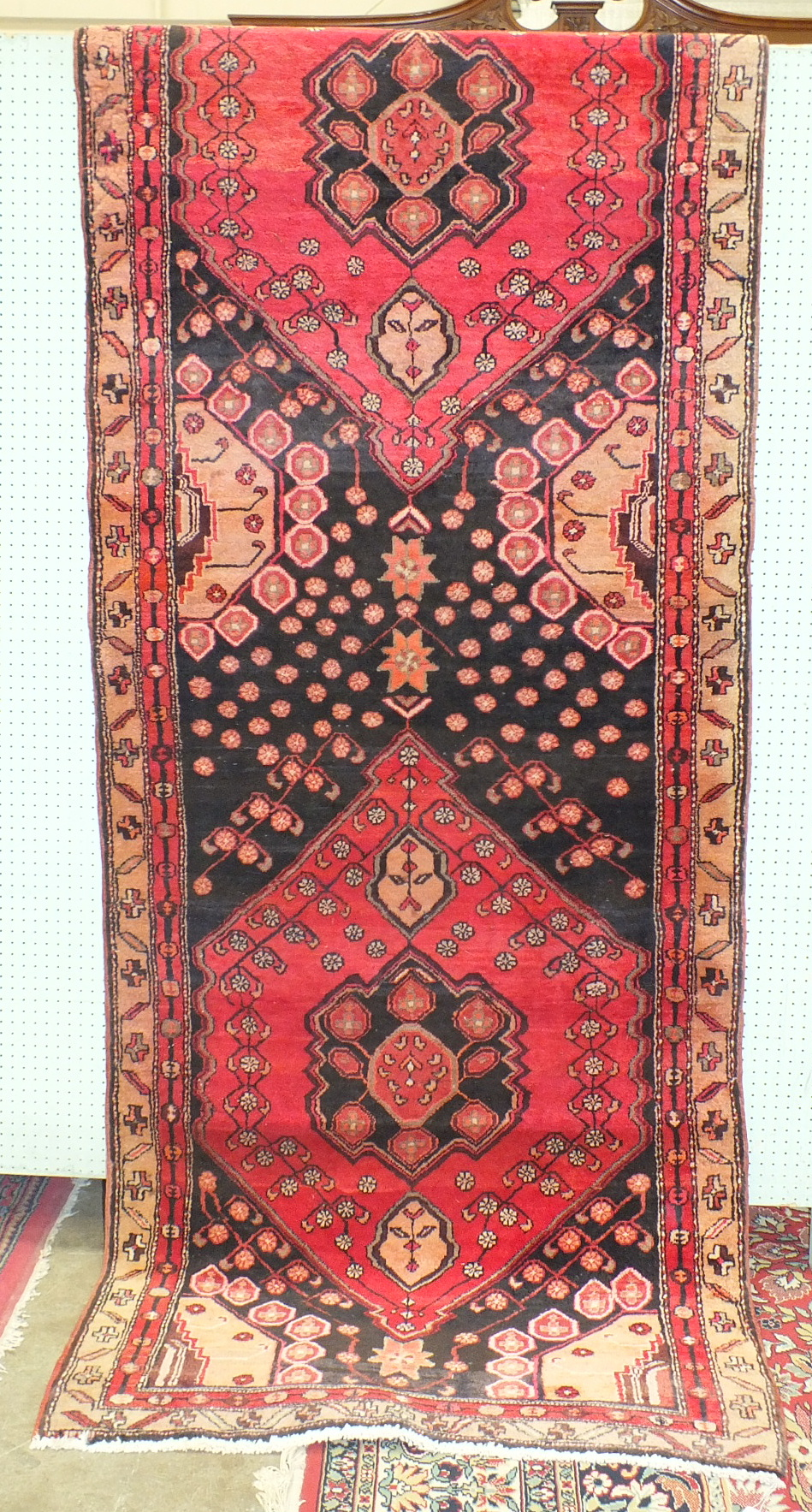 Lot 44 - A Persian runner with two red medallions on a black ground, 102 x 307cm.