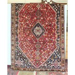 A Persian Qashqai rug with long and central symmetric design on red and blue ground, 156 x 250cm.