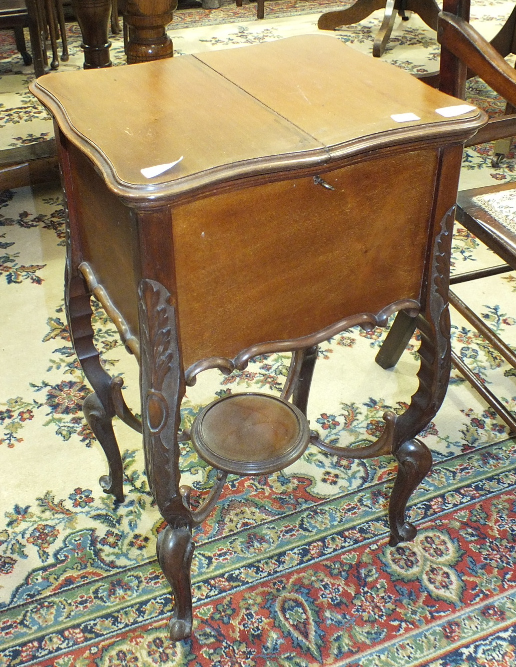 Lot 3 - A mahogany work table fitted with a double hinged top, on carved shaped cabriole legs united by an