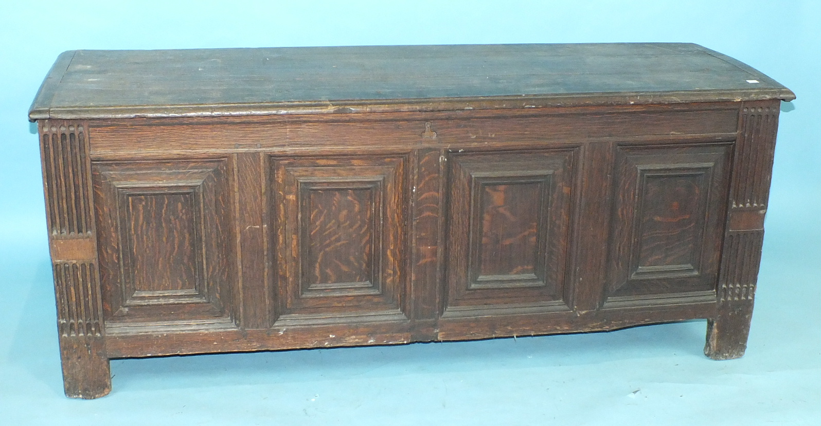 Lot 17 - A large antique oak panelled coffer, the fielded panels within reeded stiles extended to form