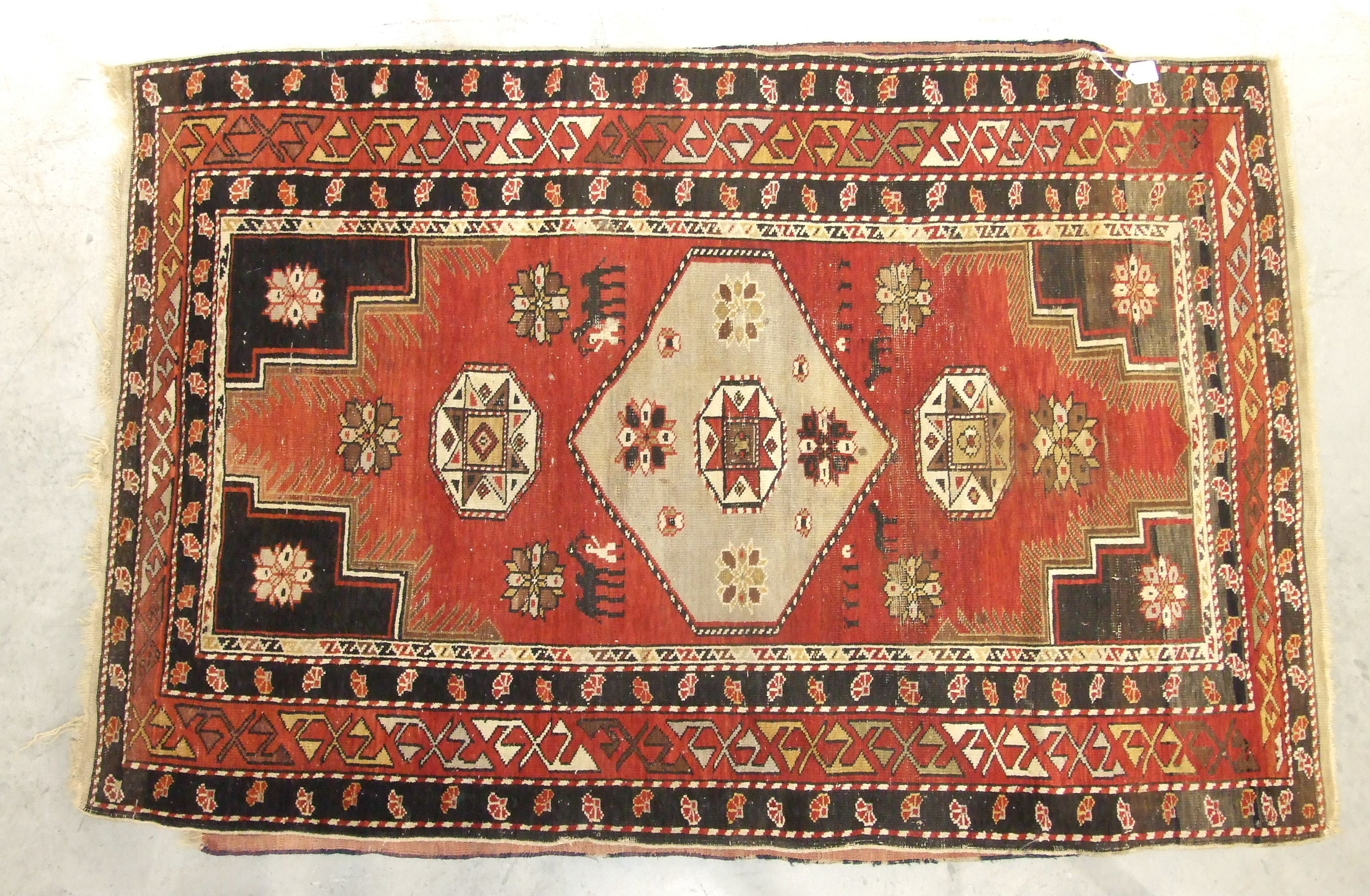 A mid-20th century wool rug, red field with central hexagonal medallions, figures leading camels and