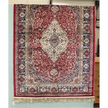 A modern Kashmir rug with central ivory medallion on red ground, 115 x 82cm.