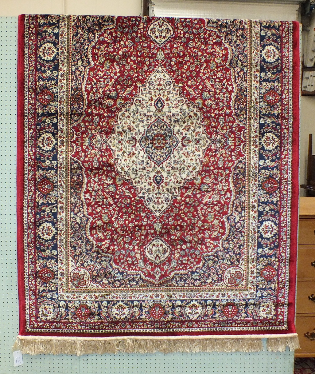 Lot 47 - A modern Kashmir rug with central ivory medallion on red ground, 115 x 82cm.