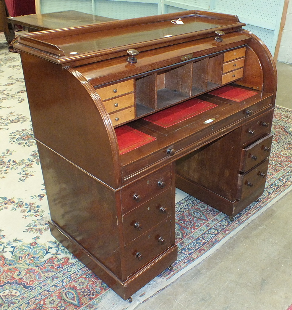 A Victorian mahogany cylinder writing desk, the pull-out desk top and fitted interior above two