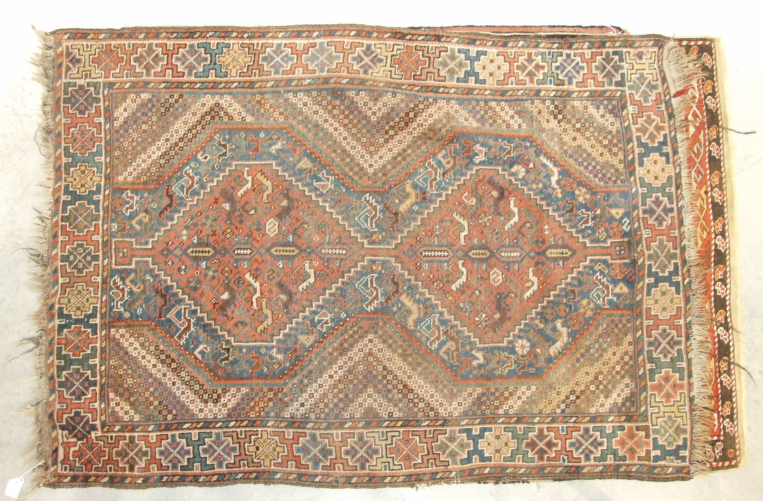 A mid-20th century wool rug, red field with central hexagonal medallions, figures leading camels and - Image 3 of 3
