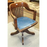 A 1920's/1930's oak revolving tilt-action office armchair with slatted back and shaped seat, on