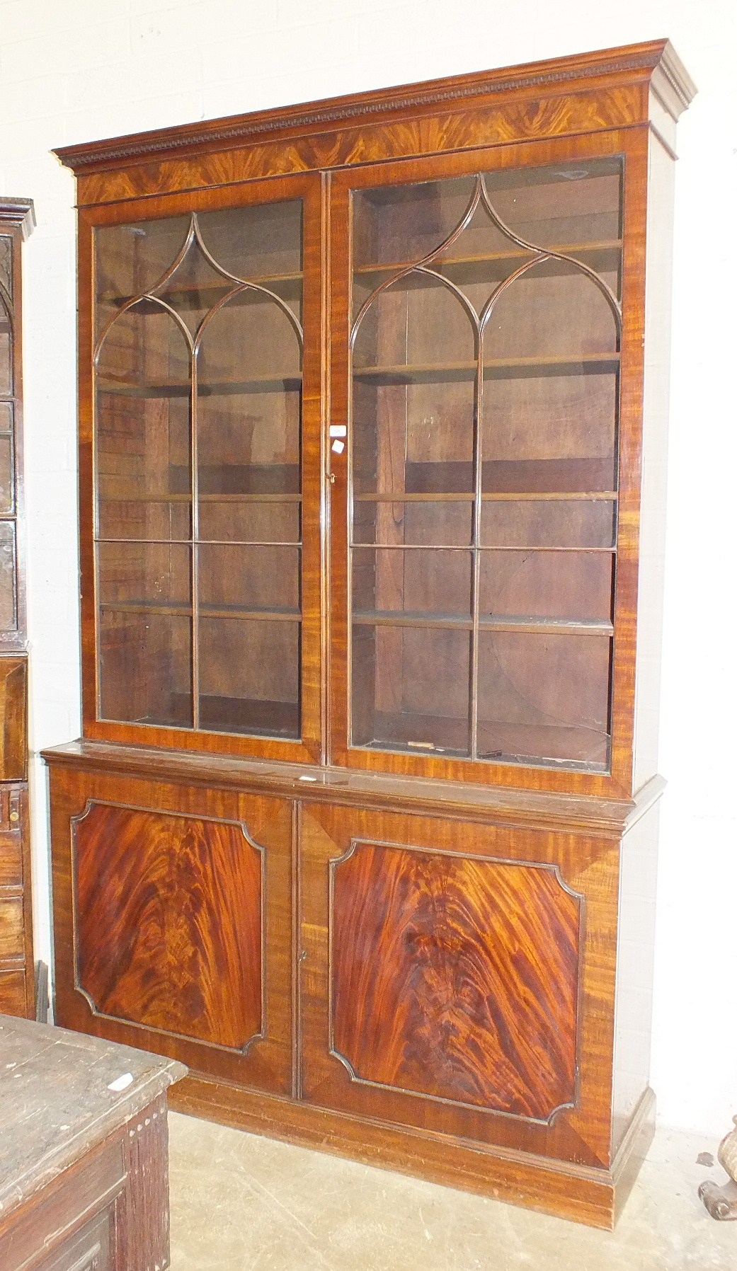 Lot 16 - A reproduction mahogany Georgian bookcase, the dentil cornice above a pair of astragal-glazed