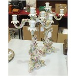 A pair of late-19th century Continental porcelain four-branch candelabra formed as cherub