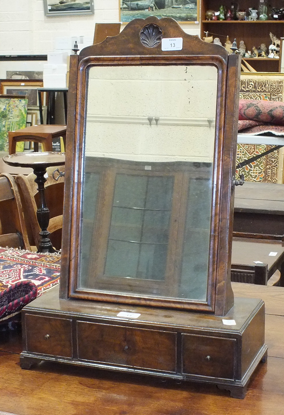 A Queen-Anne-style walnut dressing glass, the rectangular base fitted with three drawers, on bracket