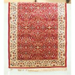 A similar rug with all-over foliate design, on red ground with ivory border.