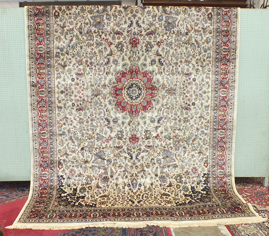 A large Kashmir rug with overall foliate design, on an ivory ground within multiple border, 340 x
