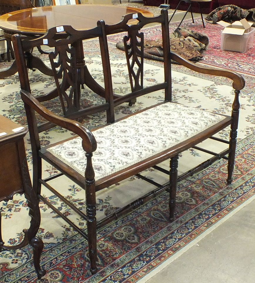 An Edwardian stained wood two-seater hall settee with padded seat, on turned front legs, 103cm