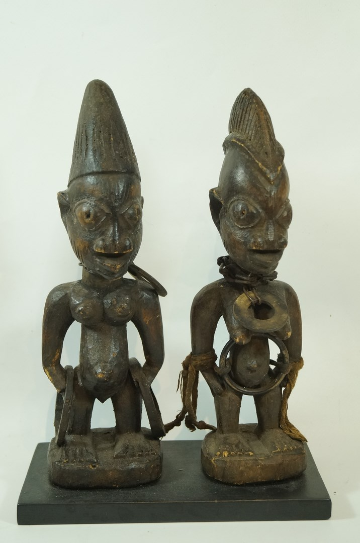 Lot 41 - Two carved wooden tribal figures, set on a modern stained pine plinth, 28.