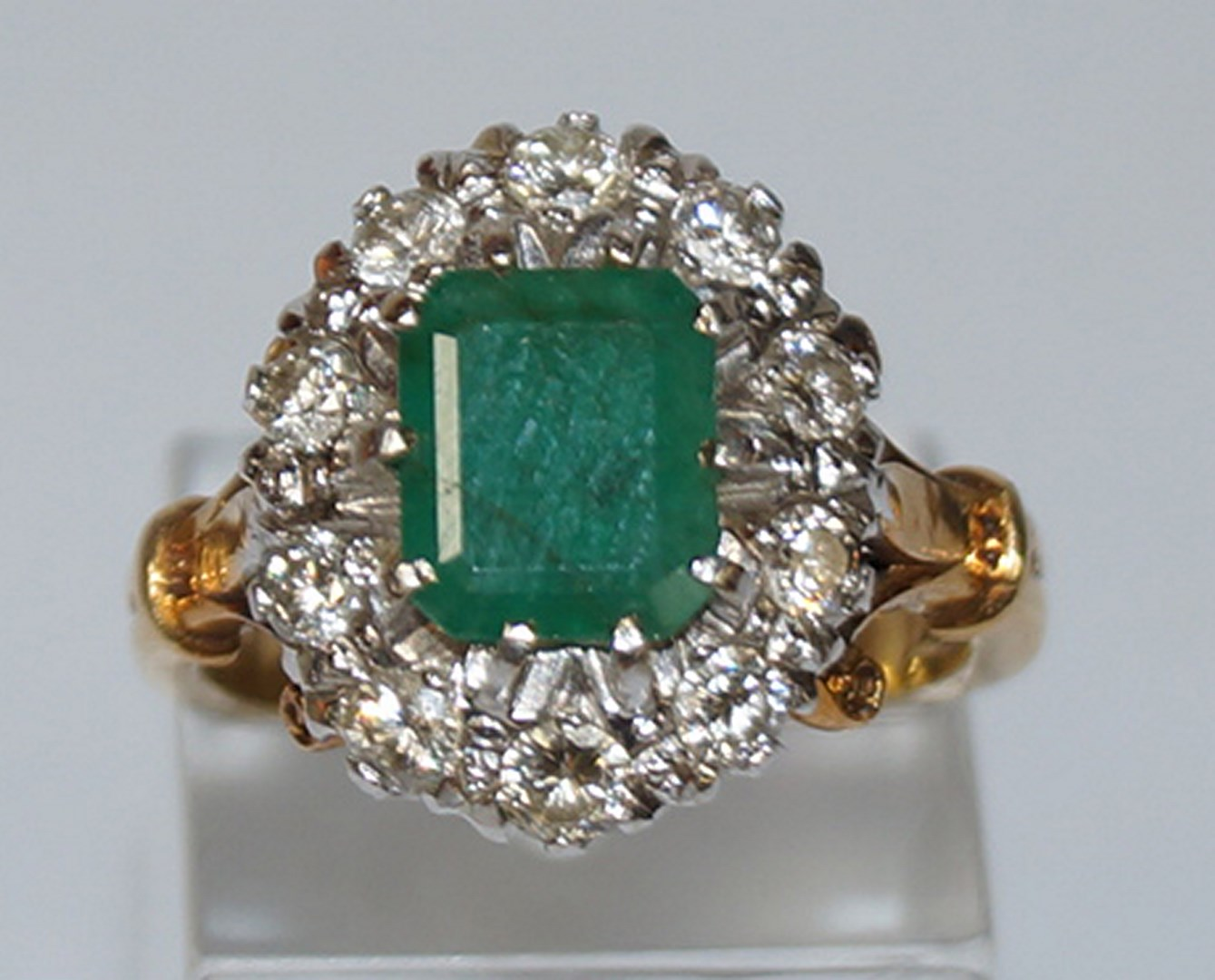 Lot 47 - An emerald and diamond 18 carat gold cluster ring,