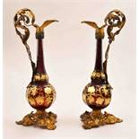 A pair of Victorian ruby glass and gilt metal mounted ornamental ewers,