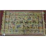A Persian Qum style rug depicting a hunting scene with deer, set on an ivory field within a