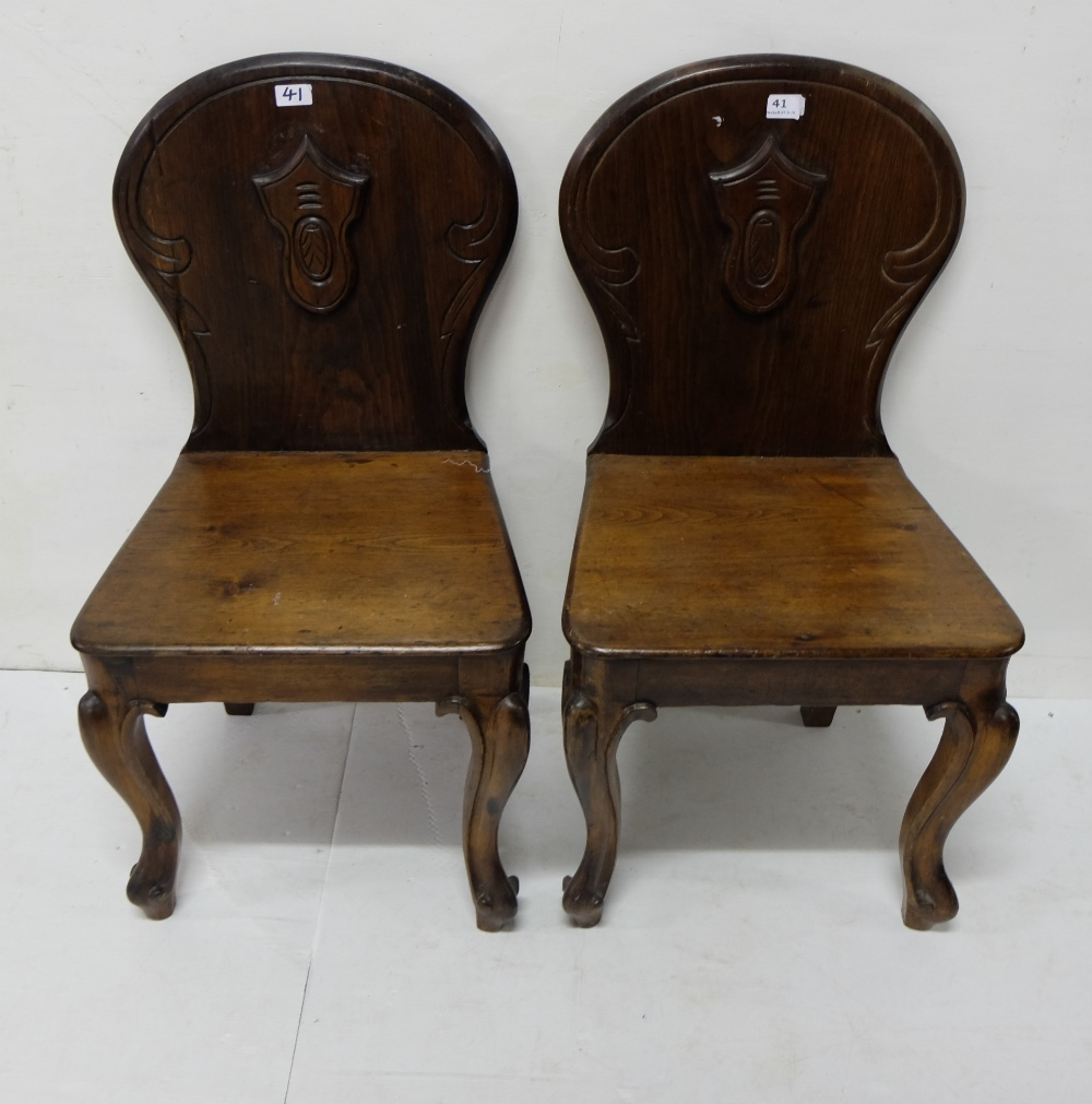 Lot 41 - Matching pair pitch pine, mahogany finish Hall Chairs, shield backs with cabriole front legs and